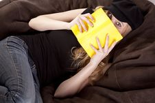 Woman On Bean Bag Looking Behind Book Stock Photos