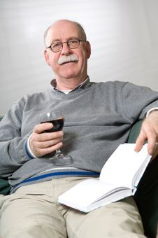 Free Senior Man Is Reading A Book With A Glass Wine Stock Photo - 16923200