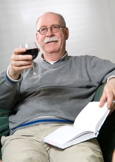 Free Senior Man Is Reading A Book With A Glass Wine Royalty Free Stock Images - 16923219