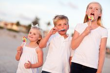 Brother And Sisters Enjoying Lollipops Outside