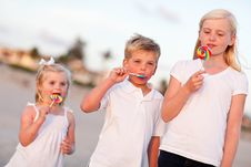 Cute Brother And Sisters Enjoying Their Lollipops