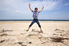 Free Boy Enjoys  The Beautiful Beach And Jumps Royalty Free Stock Image - 16943546