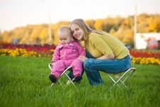 Free Woman And Cute Baby Sitting On Chairs In Park Stock Images - 16968574