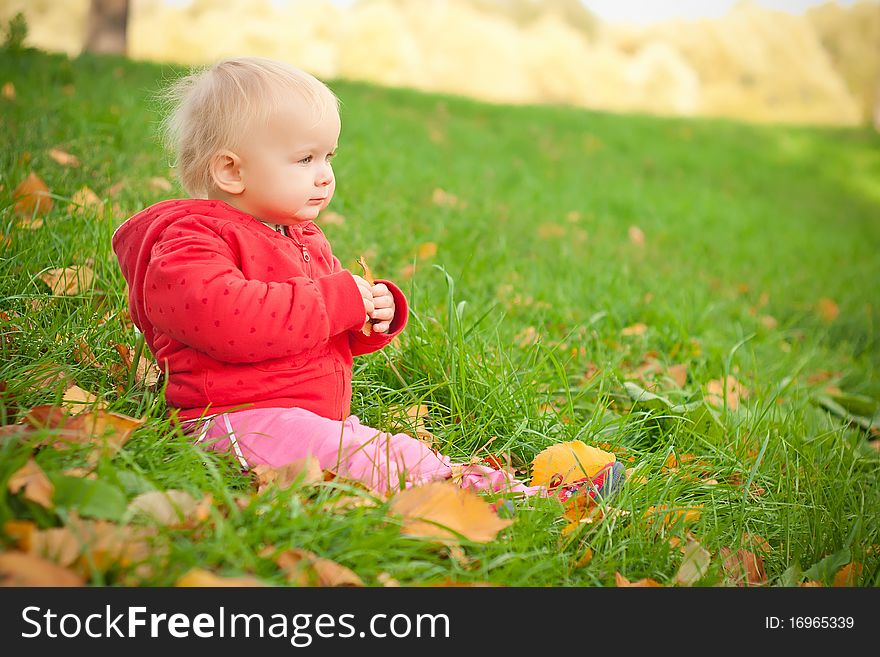 Adorable baby sit on green grass in hill