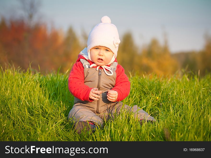Adorable baby sit near top of hill
