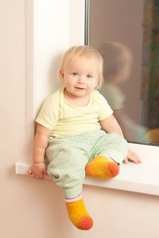 Adorable Toddler Girl Sitting On The Window Sill Royalty Free Stock Photo