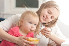 Young Mother Feeding Daughter With Porridge Royalty Free Stock Photography