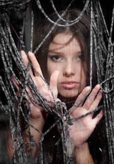 Free Young Girl Looking Through Wet Window Stock Photo - 16991310