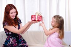 Little Girl Mom Gives A Holiday Gift Royalty Free Stock Images