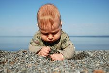 Free The Baby Digs A Hole In Sand Stock Photos - 16998983