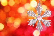 Glass Snowflake Against Red Blurred Background Stock Photography