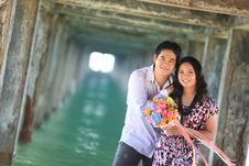 Free Couple Standing Under Pier On The Beach Stock Images - 17039034