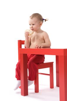 Little Baby Girl Is Sitting On The Red Chair Stock Photo