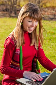 Beautiful Girl With A Laptop On The Grass Royalty Free Stock Image