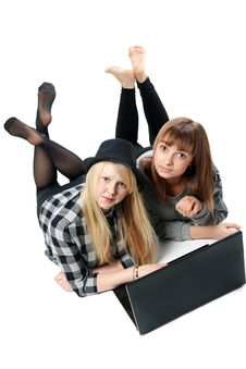 Two Girls Lies With Computer Royalty Free Stock Images