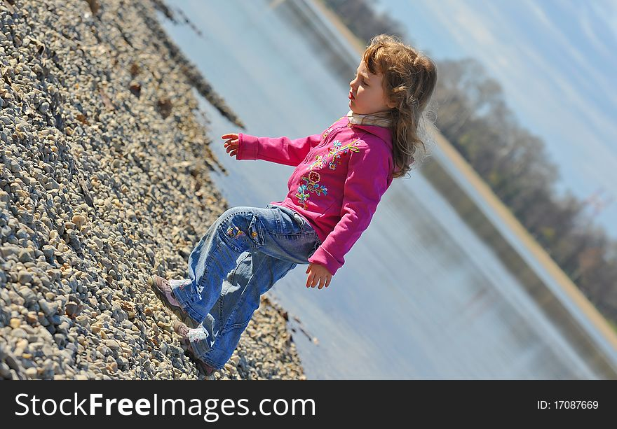 Little girl playing at the beach in winter