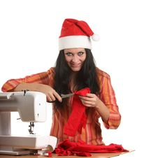 Free Seamstress In A Christmas Hat Cut Cloth Royalty Free Stock Photo - 17099035