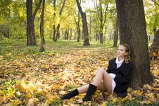 Teen Girl Sits Under The Tree In Autumn Park Stock Photos