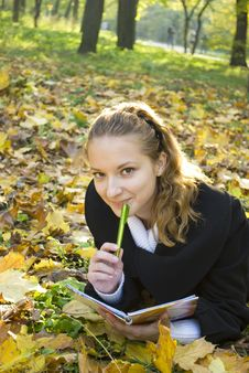Teen Girl Lies In Autumn Park With Her Diary
