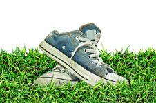Old, Dirty Sneakers Over Spring Green Grass Royalty Free Stock Photo