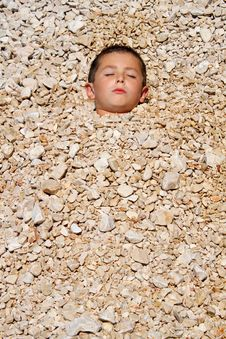 Free Boy Buried In The Pebbles Stock Image - 17116731