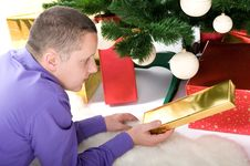 Man With Presents Under Christmas Tree Stock Photo