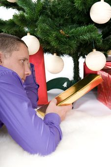 Man With Presents Under Christmas Tree Royalty Free Stock Photos