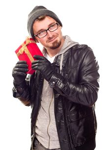 Free Curious Young Man Holding Wrapped Gift To His Ear Royalty Free Stock Photos - 17144758