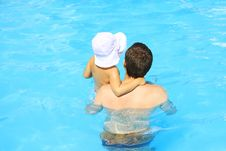 Father And Daughter Swim In The Pool Royalty Free Stock Photos