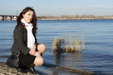Girl Sits On A Riverbank Stock Photos