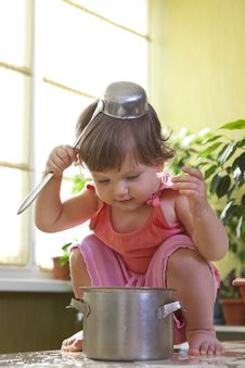 Little Girl With A Pan And Ladle On Her Head Royalty Free Stock Images