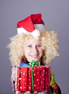 Girl In Blonde Wig And Christmas Hat Show Gift. Stock Image