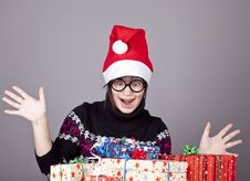 Funny Girl In Glasses With Christmas Gifts. Stock Photos