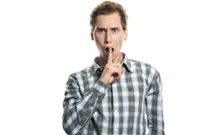 Young Man With Finger Near His Mouth Over White Stock Image