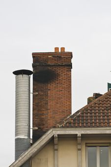 Brick Chimney And Metal Chimney On Tiled Roof Royalty Free Stock Photography