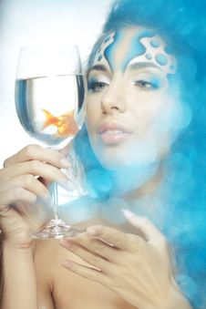 Girl With Makeup, With A Fish In A Glass Royalty Free Stock Photo