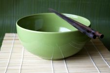 Green Bowl On Bamboo Pad Stock Photography