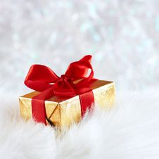 Free Golden Gift Box On White Fur Against Silver Blur Royalty Free Stock Photos - 17312648