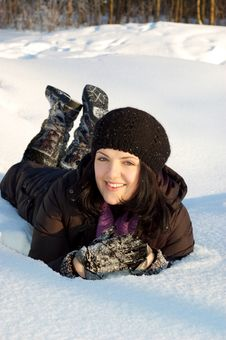 Happy Young Woman Laying In The Snow Royalty Free Stock Image
