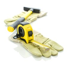 Gloves With Measuring Tape And Hammer Royalty Free Stock Photography