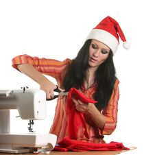 Free Seamstress In A Christmas Hat Cut Cloth Stock Image - 17372641