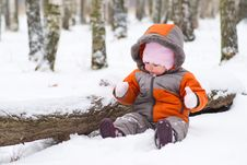 Cute Baby Sit On Snow And Play With Mittens Stock Photo
