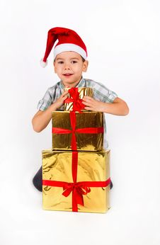 Free Little Boy In Santa Hat With A Bunch Of Gifts Royalty Free Stock Images - 17470049