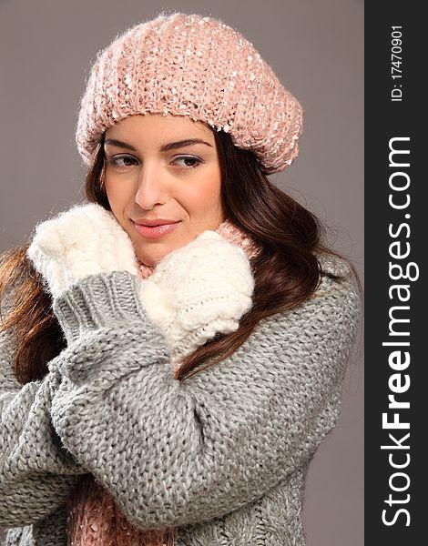 Girl in warm winter woollies looking away smiles