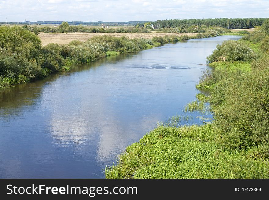 Small blue river surround the green banks.