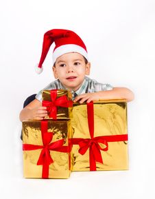 Boy In Santa Hat With A Bunch Of Gifts Royalty Free Stock Photography
