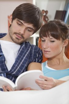 Couple Reading Book In Bed Stock Photo