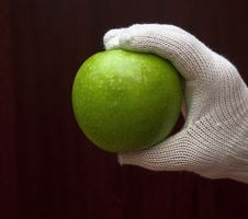 A Hand In White Glove Holding An Apple Stock Photography