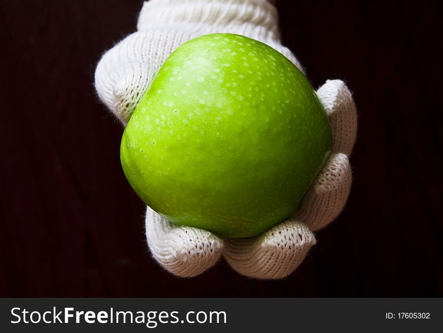 A hand in white glove holding an apple