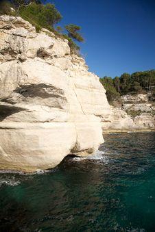 Cliff On Dark Green Sea Stock Photo